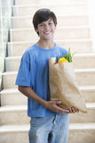 A young boy with a bag of shopping Stock Photo