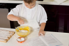 Young boy baking adding flour to the mixture Stock Images