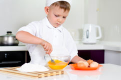 Young boy baking whipping eggs Royalty Free Stock Images