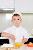Young boy baking whipping eggs Stock Photography