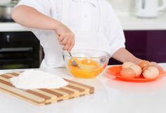 Young boy baking whipping eggs Stock Images