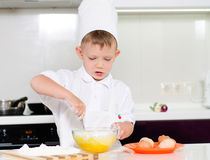 Young boy baking whipping eggs Royalty Free Stock Photography