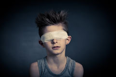 Young Boy with Bandage on Eyes Against Gray Royalty Free Stock Photos