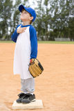 Young boy on baseball base praying Stock Photos