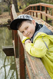 Young boy in baseball cap standing on the bridge and smiling Stock Photos