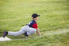 Young boy baseball player waiting on third base. A young boy baseball player humorously waiting to run to home plate during a baseball game. Ready in a sprinters Stock Image