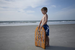 YOung Boy at the Beach. With a boogie board Stock Images