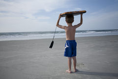 Young Boy at the Beach. Holding a boogie board over his head Stock Image