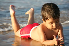 Young boy at the beach. Playing royalty free stock image