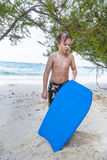 Young boy at the beach is exhausted from surfing Royalty Free Stock Photo