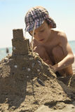 Young boy on beach making sandcastle. Young boy wearing sunhat making a sandcastle on beach on sunny day Royalty Free Stock Photography