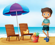 A young boy at the beach near the wooden chairs Stock Photos