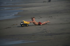 Young Boy Beach Play. A young four year old boy runs on the beach and falls surprised pushing his truck toward the surf zone Stock Photo