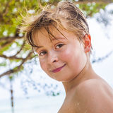Young boy at the beach is smiling and looking self confident Stock Image