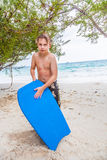Young boy at the beach with surf board looks exhausted Royalty Free Stock Photos