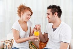Young boy and a beauty girl drinking ora Royalty Free Stock Photography