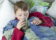 Young boy in bed taking his medicin. Young caucasian boy in bed with the flu taking his medicin Royalty Free Stock Photography