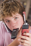 Young boy in bedroom holding many cellular phones Royalty Free Stock Image