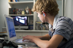 Young boy in bedroom using laptop Stock Image