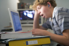 Young boy in bedroom yawning using laptop Stock Photos