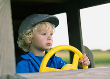 Young boy behind yellow wheel. Yong blond haired boy in grey cap and blue jacket behind yellow wheel in toy vehicle Stock Photography