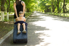 Young boy being carried on a trolley travel bag Royalty Free Stock Photography
