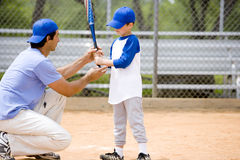 Young boy being shown how to bat in baseball Stock Images
