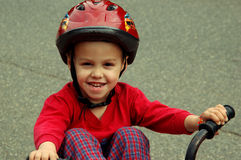 Young boy on a bicycle. Close in shot of a young child wearing a helmet sitting on his bicycle Stock Images