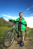 Young boy with a bicycle in nature rests. Stock Photos