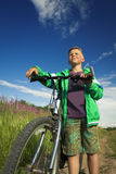 Young boy with a bicycle in nature rests. Stock Image