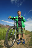 Young boy with a bicycle in nature rests. Royalty Free Stock Photo