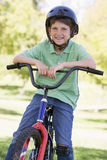 Young boy on bicycle outdoors smiling Stock Images
