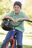 Young boy on bicycle outdoors smiling royalty free stock image