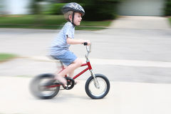 Young boy on a bike. A young boy rides his bike. This is a in-camera motion blur Royalty Free Stock Images