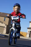 Young Boy on Bike. A young curley blonde haired boy on his first bike Royalty Free Stock Photo