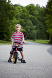 Young boy with bike in street Royalty Free Stock Photography