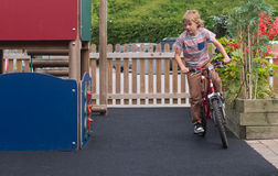 Young boy on bike. Young white male child on bike in play area royalty free stock photos