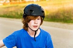 Young boy is biking and wearing a helmet Royalty Free Stock Photos