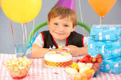 Young boy with birthday cake and gifts at party. Smiling Stock Photos