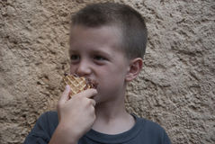 Young boy biting a chocolate ice cream cone Stock Photography
