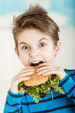 Young boy biting into a salad burger Royalty Free Stock Images