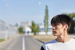 Handsome asian man on the road in a white T-shirt. Young boy with black hair posing outdoors on the street. Copy space Royalty Free Stock Photo