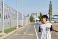 Handsome asian man on the road in a white T-shirt. Young boy with black hair posing outdoors on the street. Copy space Royalty Free Stock Images