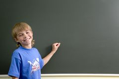 Young boy and blackboard Royalty Free Stock Images