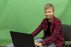 Young boy blogger records video on a green background. A boy blogger records a video on a green background at home on a video camera. A blogger is sitting on a Royalty Free Stock Image