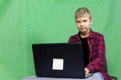 Young boy blogger records video on a green background stock photo