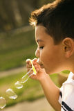 Young Boy Blowing Bubbles Stock Image