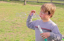 Young boy blowing bubbles Stock Photos