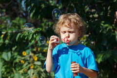 Young boy blowing a bubbles outdoors on sunny day Stock Photo