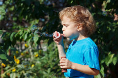 Young boy blowing a bubbles outdoors on sunny day Royalty Free Stock Images